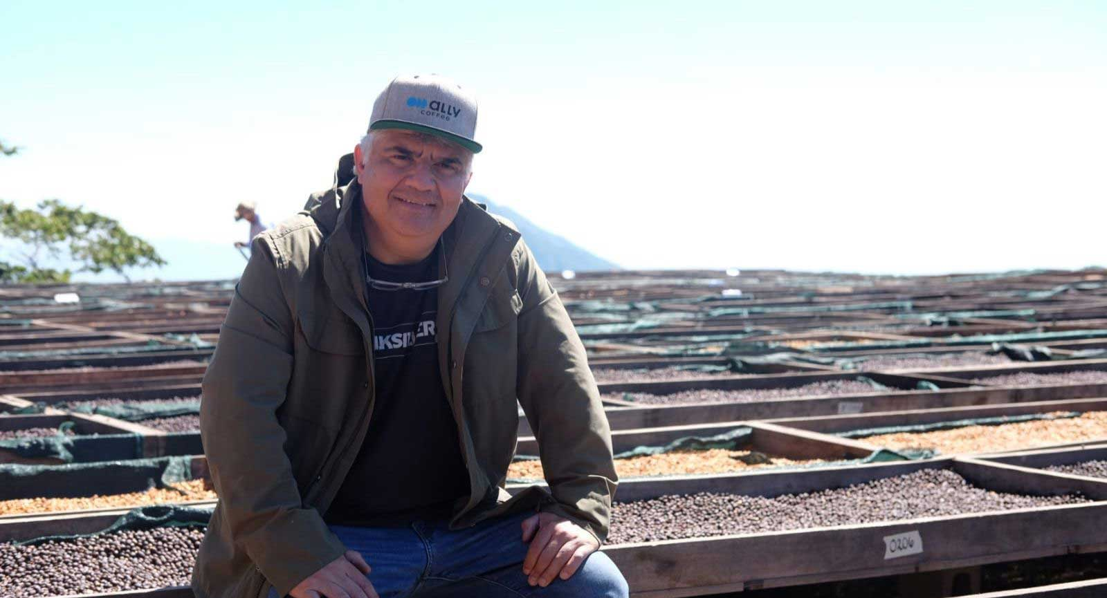 Gilberto Barona sitting with his coffee drying beds at his farm Los Pirineos in El Salvador.
